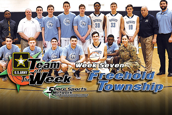 The Freehold Township boys basketball team accepts their Team of the Week game ball from U.S. Army Sgt. Jelissa Torres. (Photo by Steve Meyer)