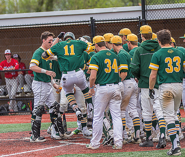 Aaron Ahn touches home plate while surrounded by his RBC teammates. (Photo by Paula Lopez)